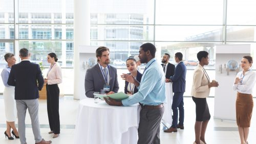 Business people discussing over documents at table during a seminar